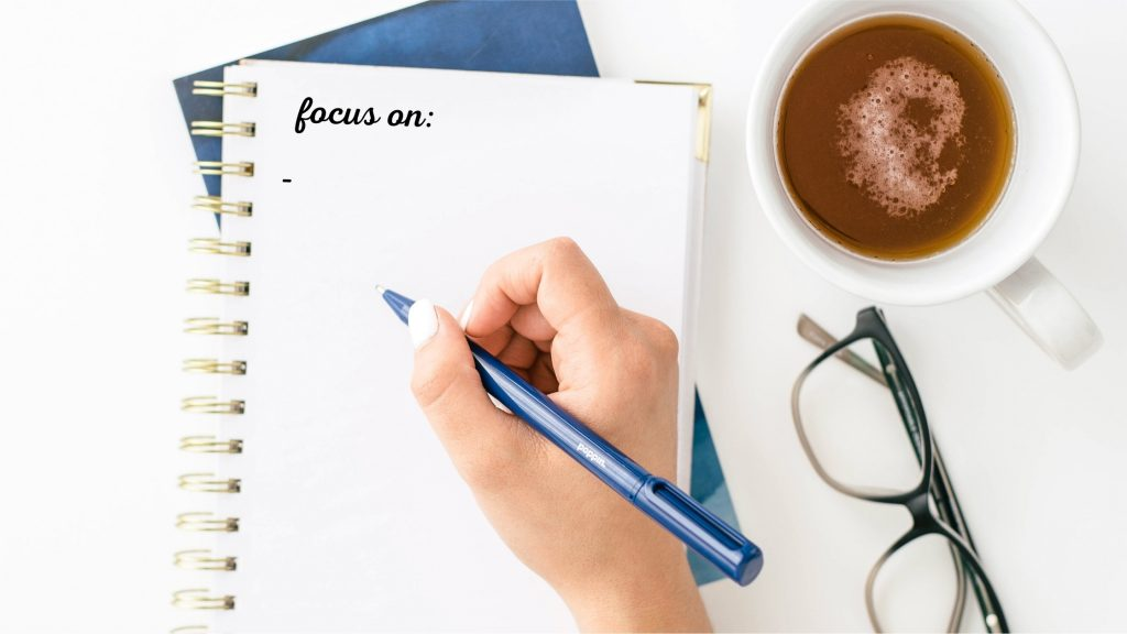 woman taking notes on what to focus on during the first month of blogging